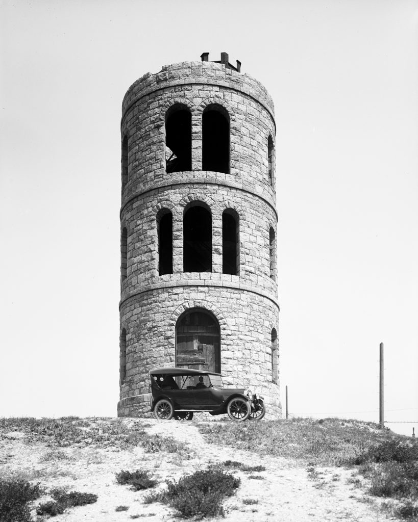 An Oldsmobile parked at the base of Anderson Tower, which was razed in 1932, on A Street, 1919